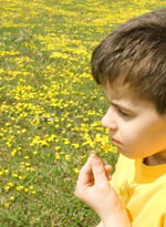 Мальчик нюхает цветок